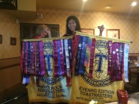 Vivien holding two of our captive banners. The fruits of club raiding!